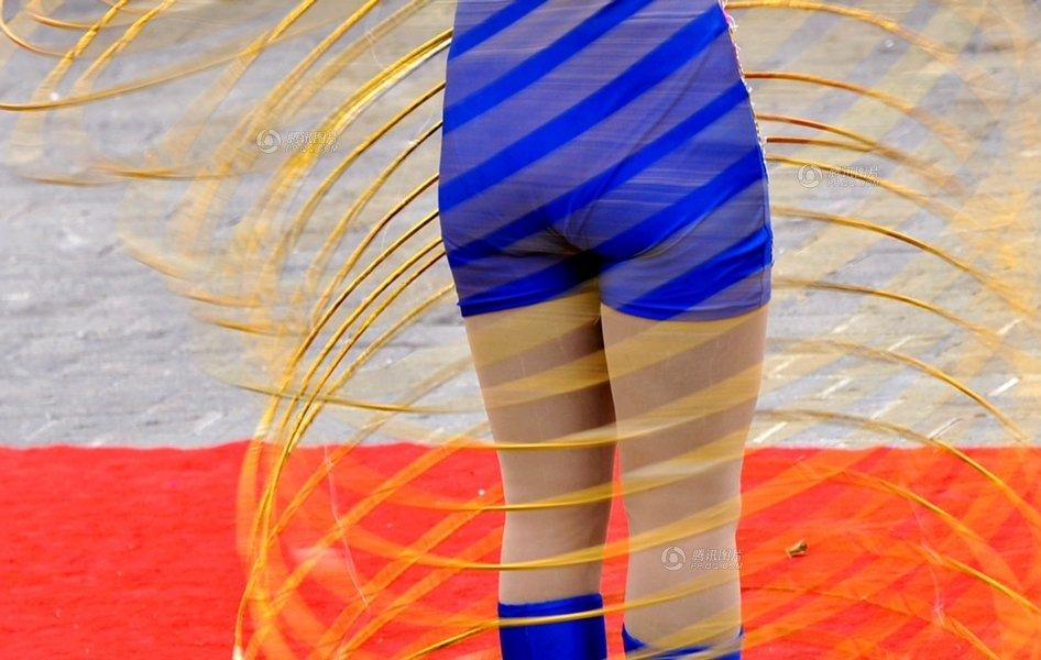 2012年2月3日,贵阳观山湖公园,一个女杂技演员表演同时摇动几十个呼啦圈