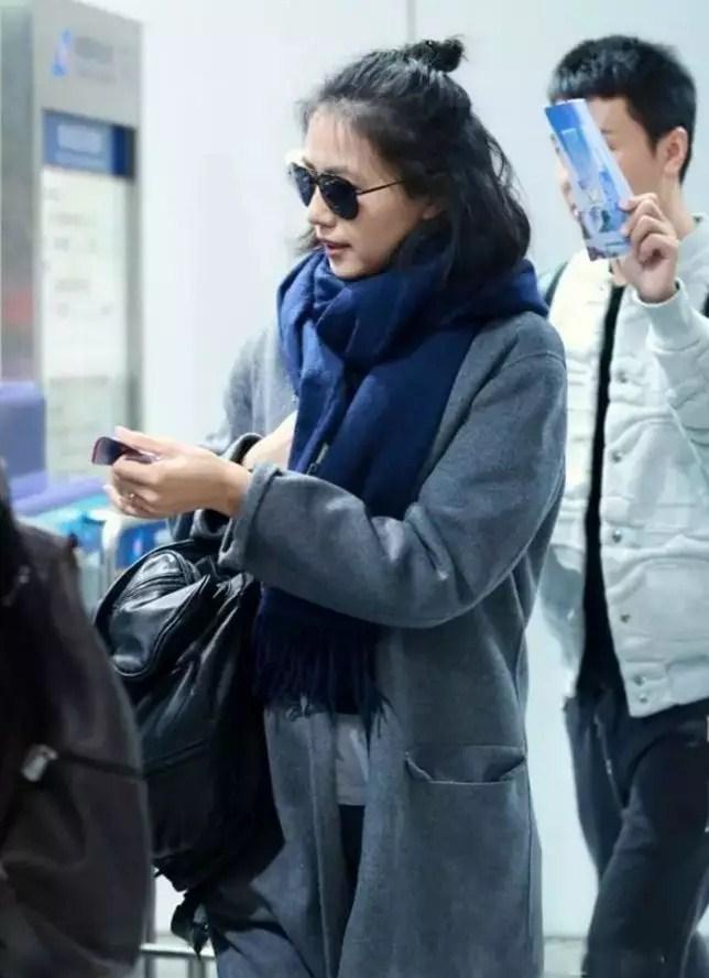 高圆圆现身机场,蓝色围巾搭配整体的纯色简约风穿搭,干净大气