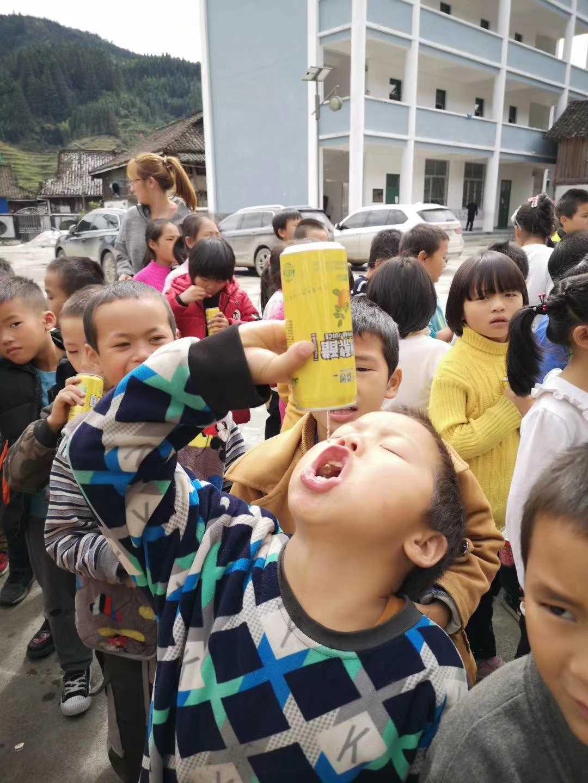 2019年10月千禧园集团董事长杨胜东到黔东南州从江县载宰便镇友娘小学开展暖冬活动现在,一名小学生拿到赠送的千禧园苹果醋,喝得如醉入梦,很是享受